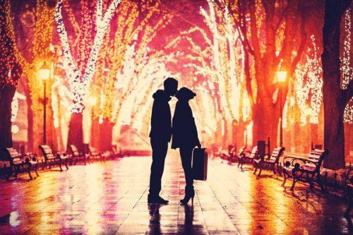 Couple kiss uder Christmas decorations